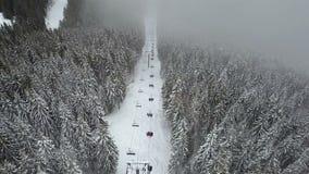 Um elevador de esqui em uma floresta em uma estância de esqui aumenta povos para a parte superior da montanha vídeos de arquivo