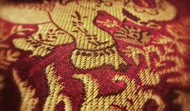 Um emblema do ouro de um elefante em um fundo vermelho Imagens de Stock