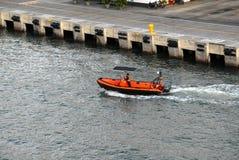 Um empregado da autoridade portuária em um bote que verifica a área de doca imagens de stock