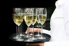 Um empregado de mesa com vidros do champanhe em uma bandeja. Imagens de Stock