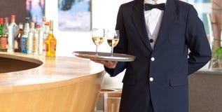 Um empregado de mesa que prende uma bandeja com vidros de vinho branco Fotografia de Stock