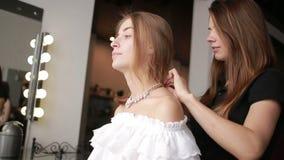 Um empregado de um cliente do salão de beleza a colar do vestido Olhar da forma vídeos de arquivo