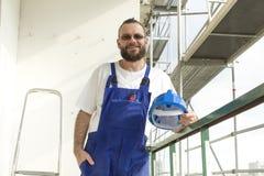 Um empregado em um equipamento do trabalho em um canteiro de obras Trabalhos na altura Fotografia de Stock