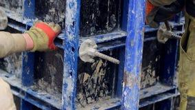 Um empregado na construção com a ajuda das torções de um martelo que fixam o apoio concreto video estoque