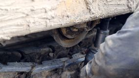 Um empregado repara uma escavadora Reparo do equipamento de construção pesado no canteiro de obras filme
