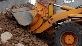 Um empurrador amarelo recolhe pedras com a areia em uma cubeta da peneiração, em um close-up, no carregador e nas pedras filme