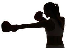 Um encaixotamento caucasiano da mulher que exercita no isola do estúdio da silhueta Imagem de Stock