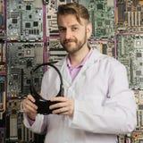 Um engenheiro eletrónico novo está com uma lupa em suas mãos perto da parede dos cartões-matrizes fotografia de stock