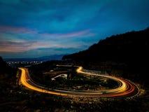 Um enrolamento da estrada no meio da montanha na noite fotografia de stock royalty free