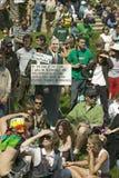 Um entalhe de George W Bush que diz a missão realizou suportes na frente de uma multidão de protestadores em um gramado da grama  Fotos de Stock