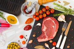 Um entrecote cru fresco da carne com os ingredientes a cozinhar vidros saborosos do jantar, do vinho tinto e de vinho, vista supe foto de stock royalty free