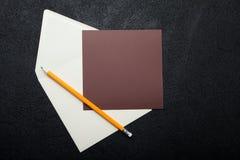 Um envelope quadrado e um papel de embalagem marrom para escrever em um fundo preto Espa?o vazio para o texto fotos de stock royalty free