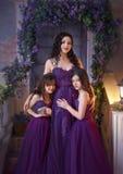 Um equipamento bonito da família Duas filhas abraçam a mamã com amor e a ternura em roxo-Borgonha luxuoso veste-se Imagem de Stock