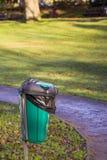Um escaninho de desperdício do cão em um parque local imagem de stock