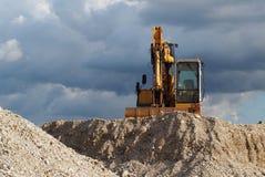 Um escavador sobre uma duna do cascalho Fotos de Stock Royalty Free