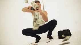 Um eslavo squatting antiquado em uma camiseta de alças e em um tampão do menino do padeiro que sentam-se com um dinheiro de jogo  video estoque
