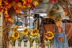 Um espantalho com girassóis e as folhas coloridas imagem de stock royalty free