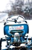 Um esparadrapo para carro do orgulho do fazendeiro no assento de um trator azul velho Foto de Stock Royalty Free