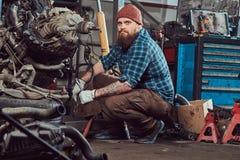Um especialista farpado tattooed brutal do mecânico repara o motor de automóveis que é aumentado no elevador hidráulico na garage fotografia de stock