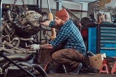 Um especialista farpado tattooed brutal do mecânico repara o motor de automóveis que é aumentado no elevador hidráulico na garage fotos de stock