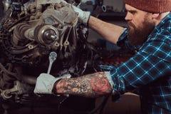 Um especialista farpado tattooed brutal do mecânico repara o motor de automóveis que é aumentado no elevador hidráulico na garage imagem de stock