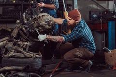 Um especialista farpado tattooed brutal do mecânico repara o motor de automóveis que é aumentado no elevador hidráulico na garage foto de stock
