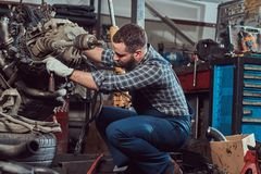 Um especialista farpado tattooed brutal do mecânico repara o motor de automóveis que é aumentado no elevador hidráulico na garage fotos de stock royalty free