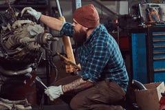 Um especialista farpado tattooed brutal do mecânico repara o motor de automóveis que é aumentado no elevador hidráulico na garage imagens de stock royalty free