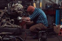 Um especialista farpado tattooed brutal do mecânico repara o motor de automóveis que é aumentado no elevador hidráulico na garage imagem de stock royalty free