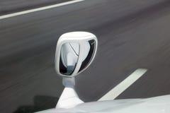Um espelho do para-choque no carro ao conduzir em uma estrada Fotografia de Stock Royalty Free