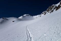 Um esqui que visita a trilha que conduz à passagem de montanha alpina Imagens de Stock Royalty Free