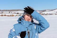 Um esquiador da moça é obstruído por uma mão do sol, está em um lago congelado neve-branco na perspectiva da vila imagem de stock royalty free