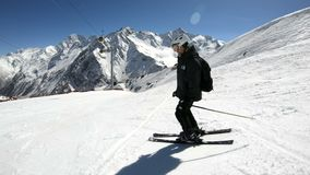 Um esquiador masculino do ângulo largo envelhecido no equipamento preto e no capacete branco com passeios dos polos de esqui em u video estoque
