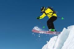 Um esquiador no material desportivo completo salta no precipício da parte superior da geleira na perspectiva do azul Imagens de Stock