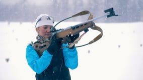Um esquiador pega um rifle ao tiro, fim vídeos de arquivo