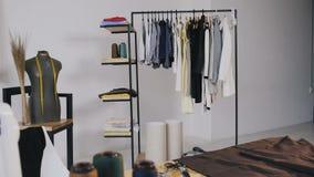 Um estúdio do desenhador de moda para costurar a roupa que o tem máquina de costura, linhas da bobina, vários artigos da costura  vídeos de arquivo