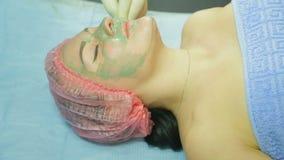 Um esteticista nas luvas remove uma máscara da argila de uma cara da mulher s com uma almofada de algodão Vista lateral filme
