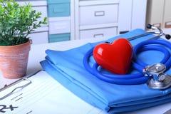 Um estetoscópio médico com coração vermelho e a prescrição de RX estão encontrando-se em um uniforme médico fotos de stock royalty free