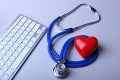 Um estetoscópio médico com coração vermelho perto de um portátil em uma tabela de madeira foto de stock