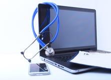 Um estetoscópio médico perto de um portátil em uma tabela de madeira, no branco imagens de stock