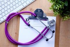 Um estetoscópio médico perto de um portátil em um de madeira Foto de Stock Royalty Free