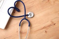 Um estetoscópio médico perto de um portátil em uma tabela de madeira, no branco imagem de stock