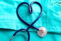 Um estetoscópio que dá forma a um coração em um uniforme médico imagem de stock