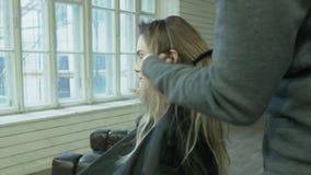Um estilista masculino profissional faz um penteado para que uma jovem mulher dispare na propaganda O cabeleireiro penteia o lour filme
