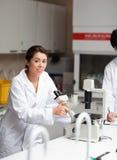 Um estudante bem parecido da ciência que usa um microscópio Fotografia de Stock Royalty Free