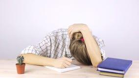 Um estudante cansado é contratado e cai assento adormecido em uma tabela com livros de texto video estoque