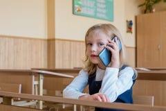 Um estudante de primeiro grau na escola fala pelo telefone emoções das estudantes fotografia de stock royalty free