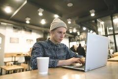Um estudante do moderno senta-se em um café e trabalha-se para uma mão em uma xícara de café O moderno senta-se em um café e usa- Imagem de Stock