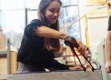 Um estudante do soprador de vidro tenta fazer uma flor fora do vidro foto de stock