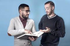 Um estudante está ajudando a seu estudante do freiend a aprender a lição Fotos de Stock Royalty Free